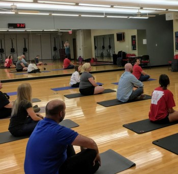 Several people sitting on yoga mats on a wood floor in a gym.