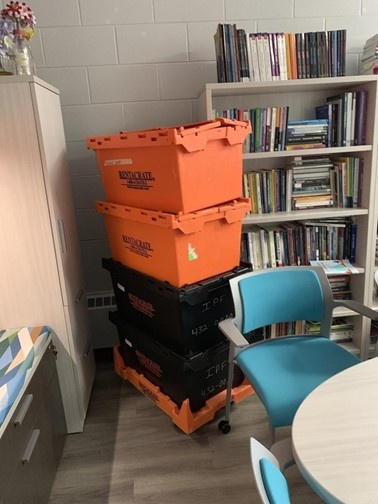 A stack of four orange and black plastic bins sits next to a messy bookshelf in our director's office. These boxes are yet to be unpacked after seven months.