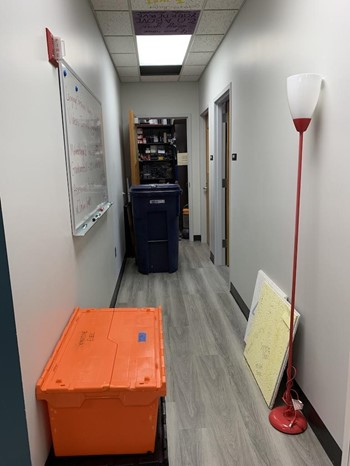 A large shredding bin, two ceiling tiles, and a broken lamp line an abandoned, messy hallway with an open supply closet in the center.