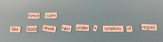 """Magnetic poetry on a blue background that says, """"Timid calm / like bold drunk rain under a symphony of regret."""""""
