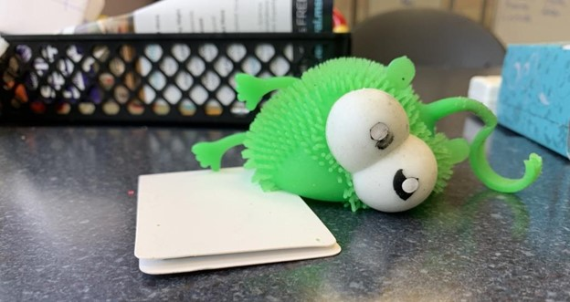 A green, squishy stress ball toy that looks like a monster with googly eyes, lying on its side, faded, dirty, germy, and broken on a table on the writing center.