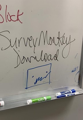 """A whiteboard that has """"Survey Monkey Download"""" handwritten on it. Below the writing, a rectangle with two dots for eyes and a squiggly mouth is drawn below, looking very melancholy."""