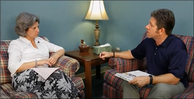 Two people sitting on plaid chairs in a living room-like setting and staring at each other, presumably in mid-conversation about motivational interviewing.