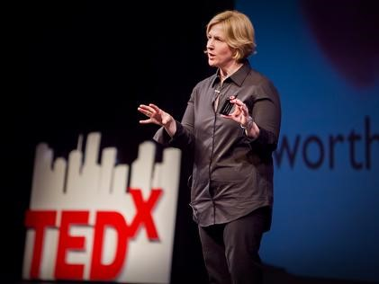 Image of woman speaking on a stage with blue background and TEDX logo