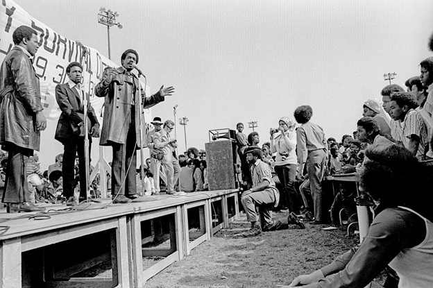 """This image depicts a black and white photograph of Bobby Seale, a young Black man with a short-cropped afro and trimmed goatee, wearing a trench coat, and speaking to a crowd outdoors. Seale stands on a wooden stage with both his hands raised while speaking into a microphone. Behind him, partially obscured by two Black men standing beside Seale, is a sign with the words """"Black Survival Conference."""" Seale's microphone is wired to a speaker at the edge of the stage, and there is a Black man kneeling beside it. There is a crowd of Black men and women seated behind, beside, and in front of the stage facing Seale."""